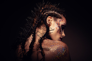Spoed Fotobehang Beauty Fashion model with bright makeup and colorful glitter and sparkles on her face and body