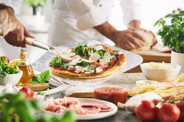 Pizza held on metal peel in kitchen