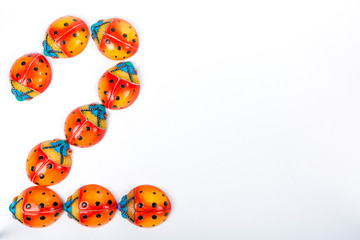 beautiful set of multicolored ladybugs forming an number 2 in Mexican ceramics, top view, copy space, flat lay, space for text