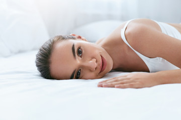 Beauty Face. Beautiful Woman With Healthy Skin On White Bed