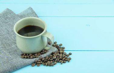 Cup of coffee with coffee beans on blue color wooden background.