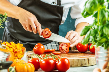 Chef slicing fresh ripe tomatoes on a board