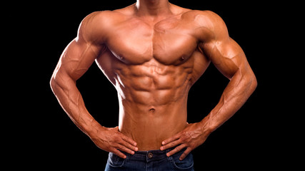 Torso of strong man in jeans against dark background. perfect abs, chest, bicep, delts