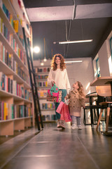 Active day. Beautiful young female looking at bookshelves while spending time in bookstore