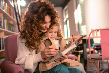 With my help. Beautiful brunette female looking at book while embracing her child