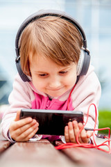 Social networks, friendship, technology and children concept. Funny portrait of little child girl with phones and headphones.