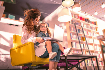 Our bookstore. Amazing blonde girl sitting on knees of mother while looking aside
