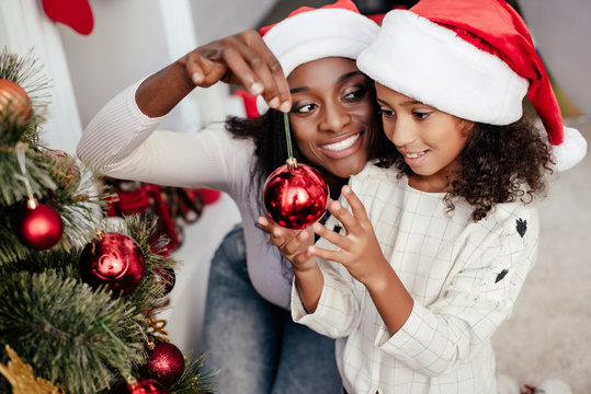 smiling african american woman in santa claus hat helping daughter to decorate christmas tree at home