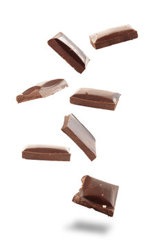 Isolated chocolate pieces falling on white background. Sweet food concept