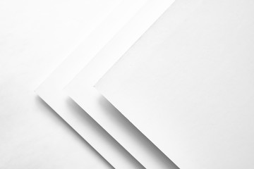White paper concept background with cardboard shadow and copy space. White geometric layer design with group of paper sheets. Flat lay