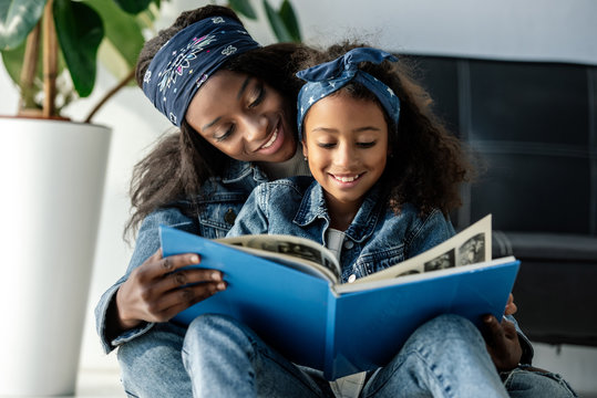 portrait of smiling african american mother and daughter looking at family photo album at home