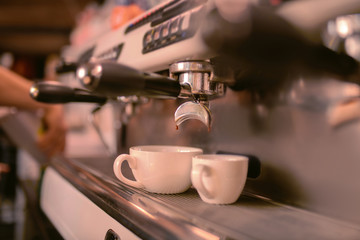 Two cups. Focused photo on modern apparatus that doing aroma coffee for guests