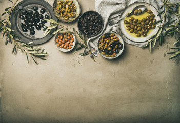 Stores à enrouleur Entree Flat-lay of various kinds of Mediterranean pickled olives in plates and bowls and olive tree branches over grey concrete table background, top view, copy space. Mediterranean meze appetizer