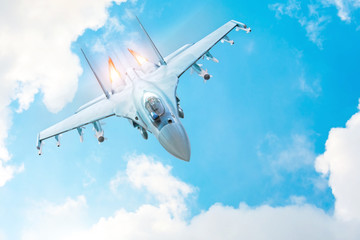 Combat fighter jet on a military mission with weapons - rockets, bombs, weapons on wings, with fire afterburner engine nozzles, flies in clouds.