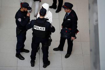 French police and a SNCF employee check train tickets during a patrol at the Gare du Nord train station as part of a security operation in Paris
