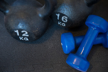 Two cast-iron kettlebells and two neoprene coated iron dumbbells, used for muscle toning, aerobic and weight training, positioned on a black mat, part of fitness classes and at-home workout routine