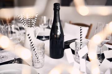 Festlich gedeckter Tisch mit schwarzer Sektflasche, Strohhalmen in schwarzweiß