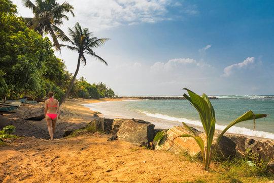 The girl is walking along the beach. Bentota, Sri Lanka, Indian Ocean.