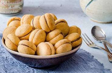 'Baci di dama': delicious chocolate cookies with hazelnuts and topping on delecate background