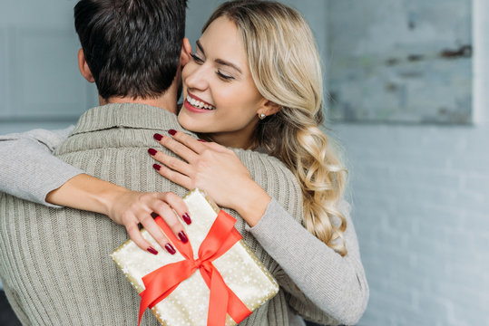 attractive young woman with gift box embracing her boyfriend at home