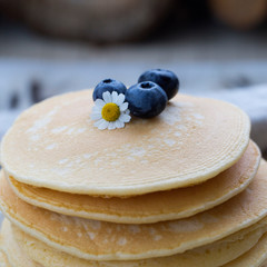 Pancakes with blueberry and camomile at gray background