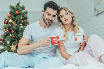 beautiful young couple with cups of cocoa sitting in bed at home on christmas and looking at camera