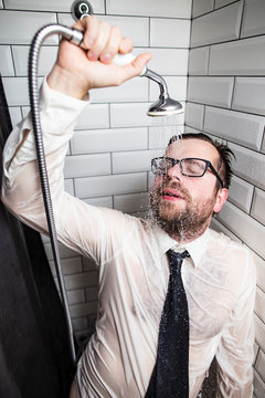 A tired bearded man with glasses, a shirt and a tie, closed his eyes and leaned on the wall in the bathroom, holding a watering can with warm running water in his hand. After a hard working day.