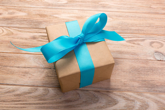 One gift box with blue ribbon wooden table background. top view