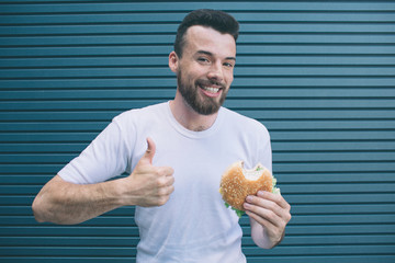 A picture of guy holding burger and showing his big thumb up. He is smiling and looking on camera. Isolated on striped and blue background.