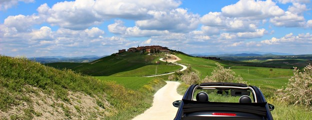 Italy: Small car in tuscan hills.