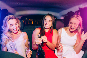 Beautiful girls are sitting in car. Brunette is opening bottle with alcohol. Blonde girls are very excited about that. Young women are holding glasses for champagne.
