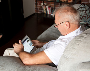 man in age uses a digital gadget while sitting on a sofa in the interior.