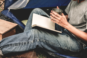 Asian young man holding glass of tea sitting is reading a book in outside the tent. Alone camping in forest.