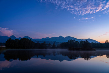 Blue hour shot of peaceful scene of beautiful autumn mountain landscape with lake, colorful trees and high peaks in High Tatras, Slovakia.
