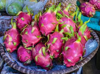 Dragonfruits at a street market stall in straw basket in Vietnam