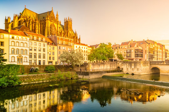 Majestic gothic cathedral of Metz on Moselle river flowing through Metz, with reflections in the water and beautiful sunset sky. France.