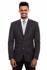 Studio shot of young  happy African businessman smiling while st