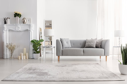 Plants and carpet in white living room interior with candles next to grey couch. Real photo