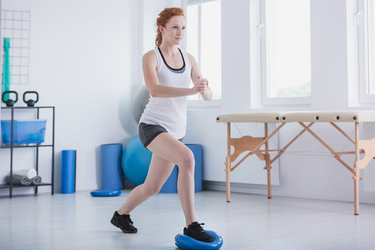 Sportswoman exercising in gymnastic room with equipment during physical workout
