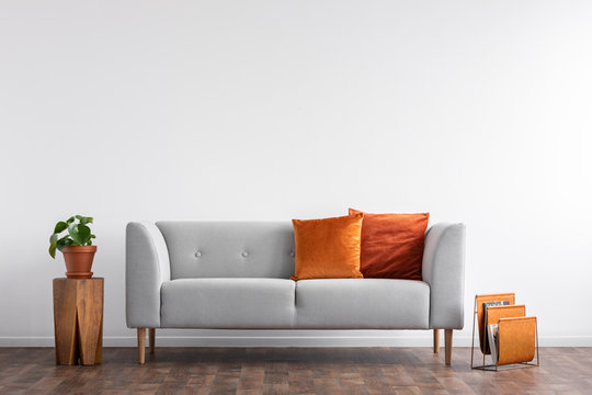 Comfortable couch with orange and red pillow in spacious living room interior, real photo with copy space on the empty white wall
