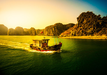 Sunset at Halong Bay Vietnam with tour boats in the foreground