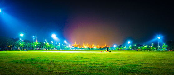 Wat Phra Kaew, Temple of the Emerald Buddha,Grand palace in night lights over green grass of Sanam Luang park at twilight in Bangkok, Thailand