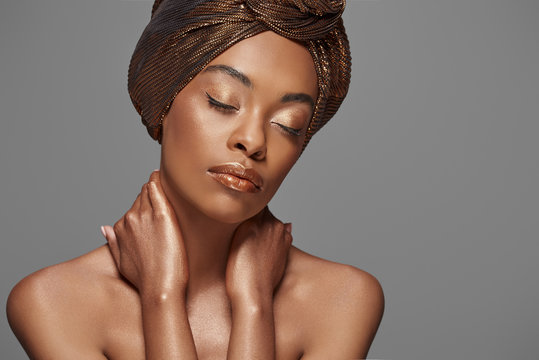 portrait of beautiful african american woman with head wrap and bare shoulders isolated on grey