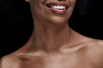 cropped shot of smiling african american woman with bare shoulders isolated on black