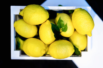 Fresh whole lemons in white wooden box, black and white background. Detox dieting, healthy lifestyle concept. Top view
