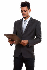 Young handsome African businessman reading on clipboard