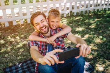 Happy and joyful family is sitting together and taking selfie. Boy is hugging his dad. Guy is holding phone and smiling on camera on the phone.