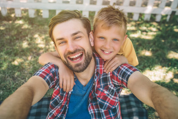 Selfie of happy and bearded guy and his son. Man is holding camera in hands and looking on it. He is smiling. His son is hugging dad and looking on camera too.
