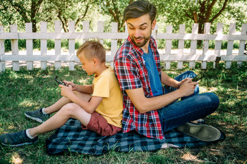 Consentrated boy is sitting back to back with his dad and playing games on phone. Dad is looking at his son and smiling. He has a phone too.