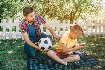 Good father is looking at his son and holding a ball. He wants to play with his son. Child is playing on phone. He doesn't want to play football.